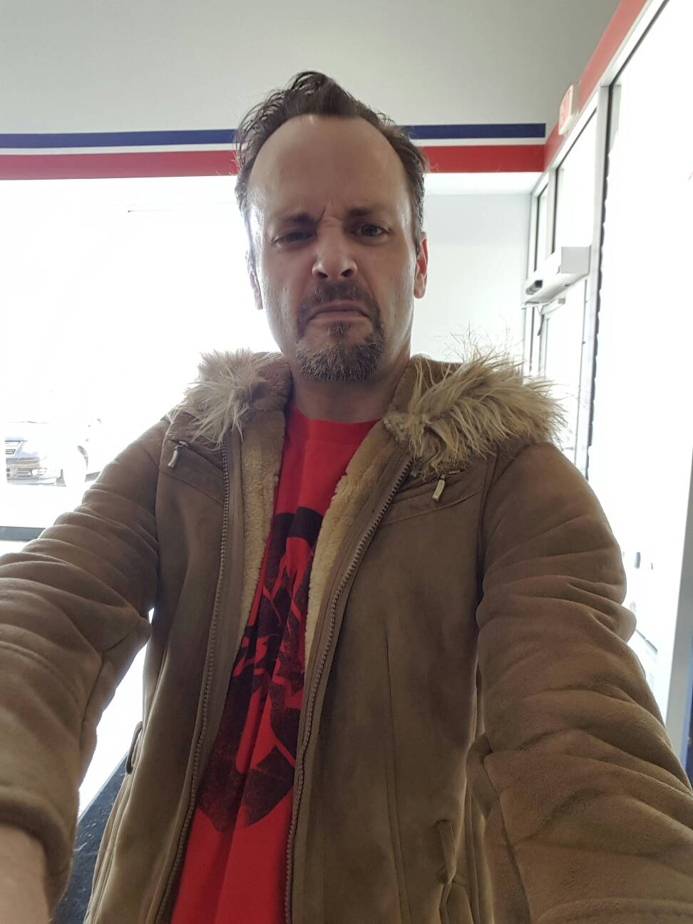 Author snarling at camera held in outstretched left arm, wearing brown seude womens jacket with fur-lined hood over a red t-shirt with black Dungeons and Dragons design.